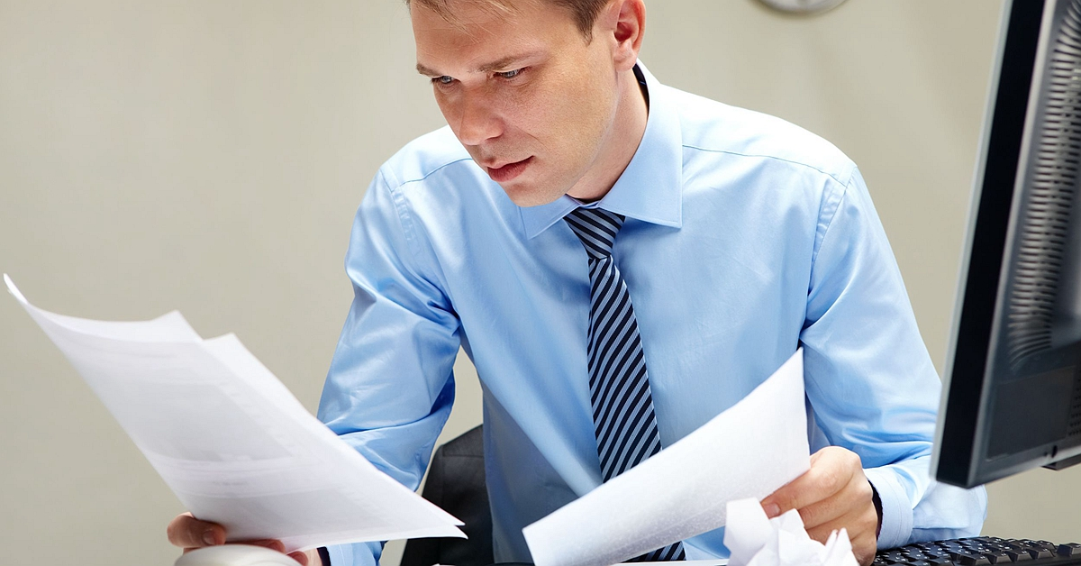9818451 - portrait of smart businessman looking through papers at workplace